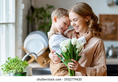 Optimistic family: mother with bouquet of  tulips laughing and touching forehead with happy son  during holiday celebration  mothers day at home