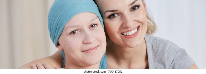 Optimistic girl with cancer wearing blue scarf with smiling sister supporting her