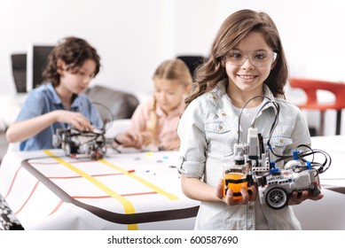 Optimistic girl demonstrating tech project at school