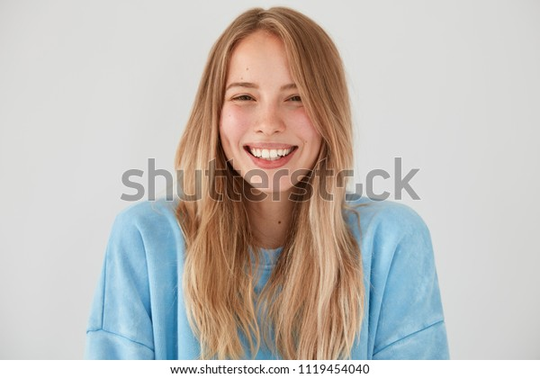 Optimistic lovely woman with charming sincere smile, being in good mood, rejoices starting new stage in life after getting married, wears casual outfit poses against white background. People, emotions