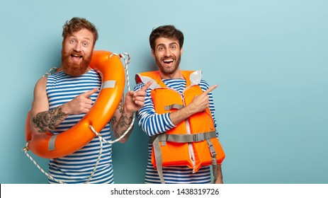 Optimistic male beach lifeguards, point right on free space for your promo work during summer day at beach, show direction, wear protective inflated life preserver, red haired man poses with lifebuoy.