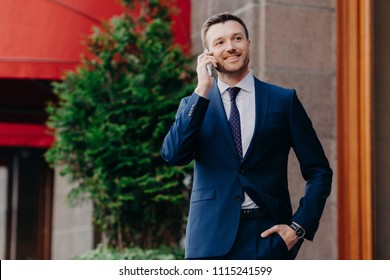 Optimistic male owner of buisness company dressed in elegant suit, has telephone conversation, consults with operator, looks into distance, has happy look, stands outside. People and communication