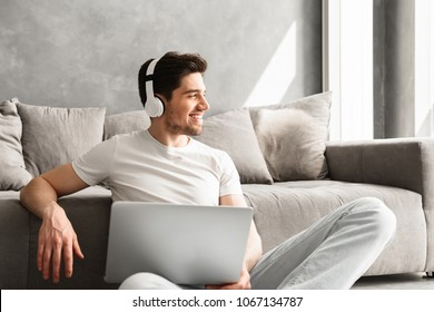 Optimistic man 30s in basic clothing sitting on floor at home and looking aside with smile while using laptop and wireless headphones