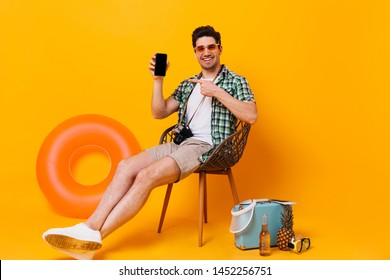 Optimistic man in green shirt and beige shorts looking into camera and showing on his smartphone. Portrait of guy in sunglasses sitting on chair with suitcase, beer, inflatable circle