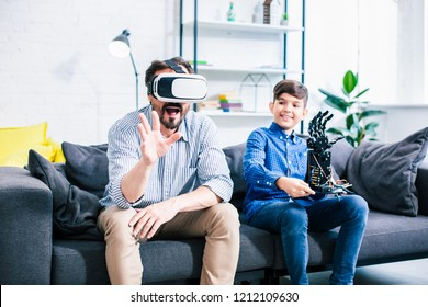 Optimistic man wearing VR glasses while testing robot with his son