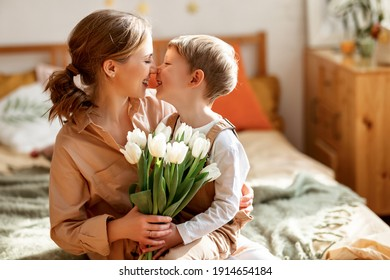 Optimistic mother with bouquet of white tulips smiling and touching noses with happy son while sitting on bed during holiday celebration mothers day at home