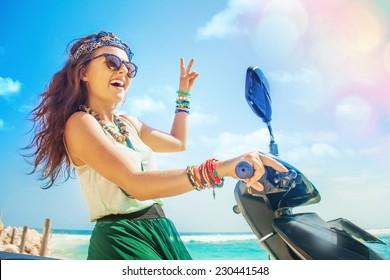 optimistic pretty hippie woman riding her motorbike