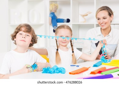 Optimistic school children cutting shapes of blotting paper during art classes, with their teacher beside