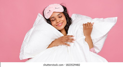 Optimistic young ethnic female in sleep mask closing eyes and hugging soft pillows during bedtime against pink background