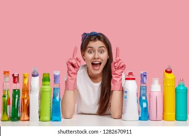 Optimistic young housemaid points upwards with both index fingers, wears headband and rubber gloves, shows something awesome on ceiling, uses various detergents, isolated on pink background.