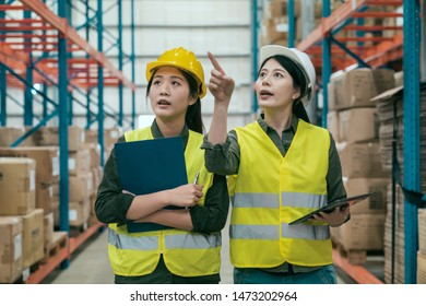 Optimization of work. Cheerful positive woman staff pointing finger while explaining ideas to coworker girl. two female workers colleagues in hats discussing and talking in large stockroom workplace.