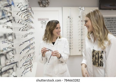 Optometrist with customer trying on glasses in optical store