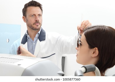 optometrist examining eyesight, woman patient pointing at the hole on plexiglass, isolated on white, ocular dominance test