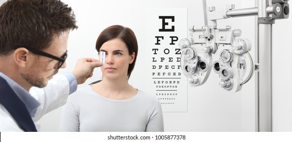 optometrist examining eyesight, woman patient pointing at the chart, eyes exam test