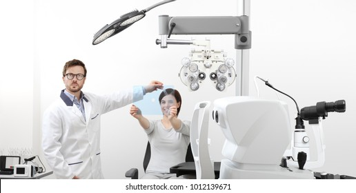 optometrist examining eyesight woman patient pointing at the hole on plexiglass in optician office, ocular dominance test