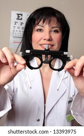Optometrist or eye doctor about to put trial frames on a patient during a vision checkup.