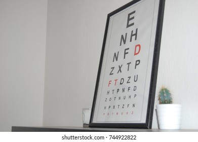 Optometrist eye test chart in a picture frame on a shelf