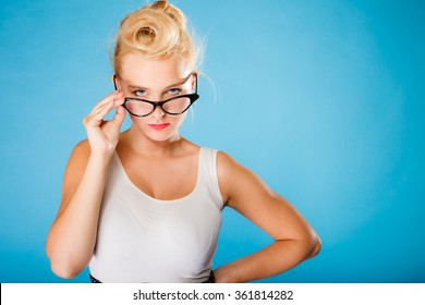 Optometrist, oculist and ophthalmologist concept. Young blonde retro pin up angry woman with eyeglasses on blue background in studio.