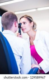 Optometry concept - handsome young man having his eyes examined by an eye doctor (color toned image; shallow DOF)