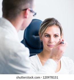 optometry concept - pretty young woman having her eyes examined by an eye doctor