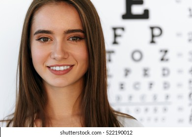 Optometry And Vision. Portrait Of Beautiful Smiling Girl Face At Opthalmologist Office. Closeup Of Happy Young Woman With Healthy Eyes And Visual Eye Test Chart On Background. High Resolution Image