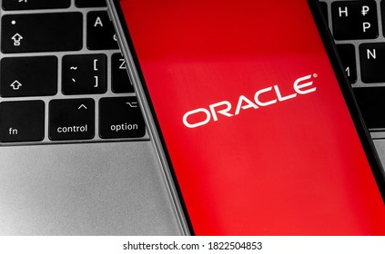 Oracle logo app on the red screen smartphone with notebook closeup. Oracle is an American multinational computer technology corporation. Moscow, Russia - September 25, 2020