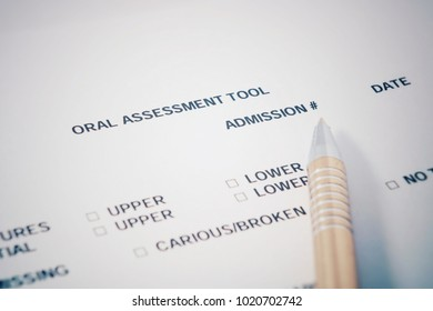 Oral assessment tool - print form for dentist. Pen lies on form.