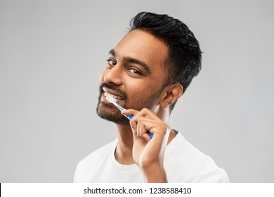 oral care, dental hygiene and people concept - smiling young indian man with toothbrush cleaning teeth over gray background