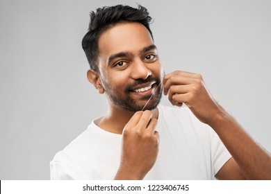 oral care, hygiene and people concept - smiling young indian man with dental floss cleaning teeth over gray background