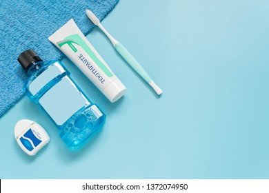 Oral care products set - Top view of dental floss, mouthwash, toothpaste, toothbrush and bath towel on light blue background. Teeth hygiene and dental health concept. Flat layout. Copy space.