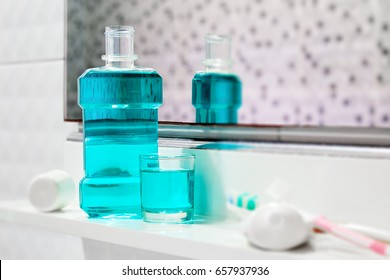 Oral cleanser for good oral health, Bottle and glass of mouthwash on bath shelf with blurred toothbrush and toothpaste in foreground