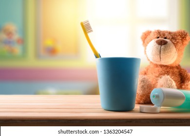 oral hygiene for children in children's room with cleaning elements on wooden table and stuffed toy. Horizontal composition. Front view