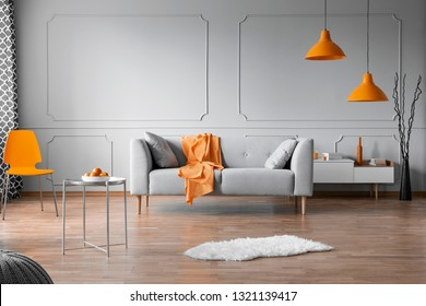 Orange accents in grey living room interior with copy space on empty wall