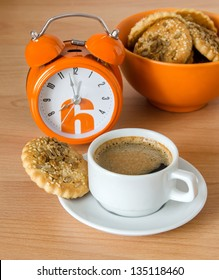 the orange alarm clock, cup of coffee and cookies are isolated on a wood background