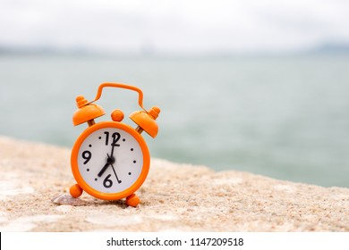 Orange alarm clock on the sea background
