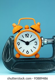 An orange alarm clock placed in a Grey clamp against a pastel purple background, asking the question do you manage your time effectively