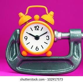 An Orange alarm clock placed on some golden coins with a purple background, asking the question how long before your investment matures?