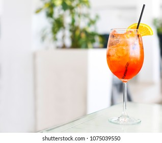 Orange alcohol cocktail with straw on white table