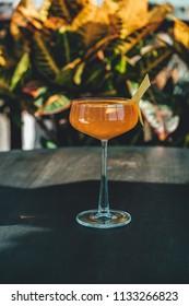 Orange alcoholic cocktail on bar table. Bartender drinks.