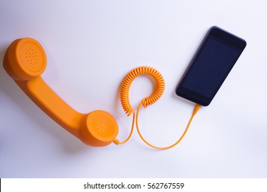 Orange analog phone and smartphone connected by a cable