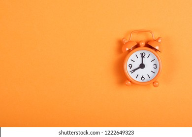 Orange analogue alarm clock showing eight in the morning on background of the same tone. Flat lay with copy space.