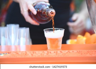 orange aperitif for spritz poured by a woman in plastic glasses during a party