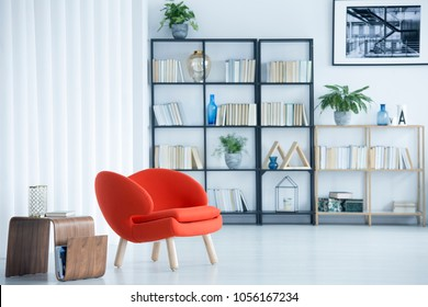 Orange armchair next to wooden table in spacious living room interior with bookshelf and poster
