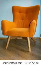 Orange armchair in a room with wooden floor