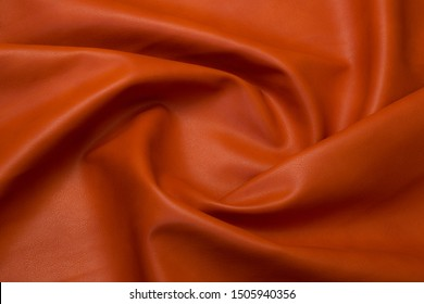 orange artificial leather with waves and folds on PVC base