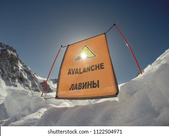 orange avalanche sign high in the mountains in the snow against the blue sky background