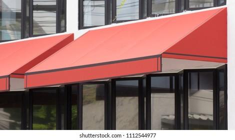 orange awning over glass windows and black aluminium frame, canvas shading