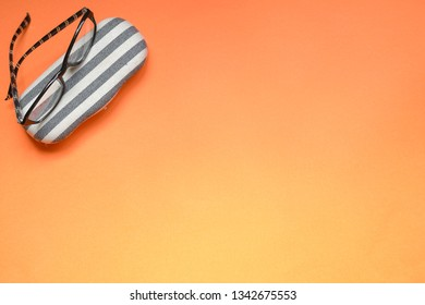 Orange background with copy space and reading glasses and its casing on the side