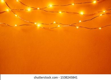 Orange background with illuminated lights of garland