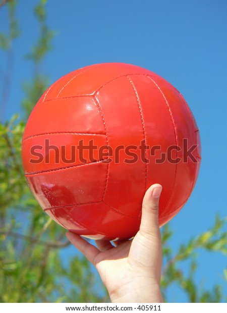 Orange ball at blue sky in hand